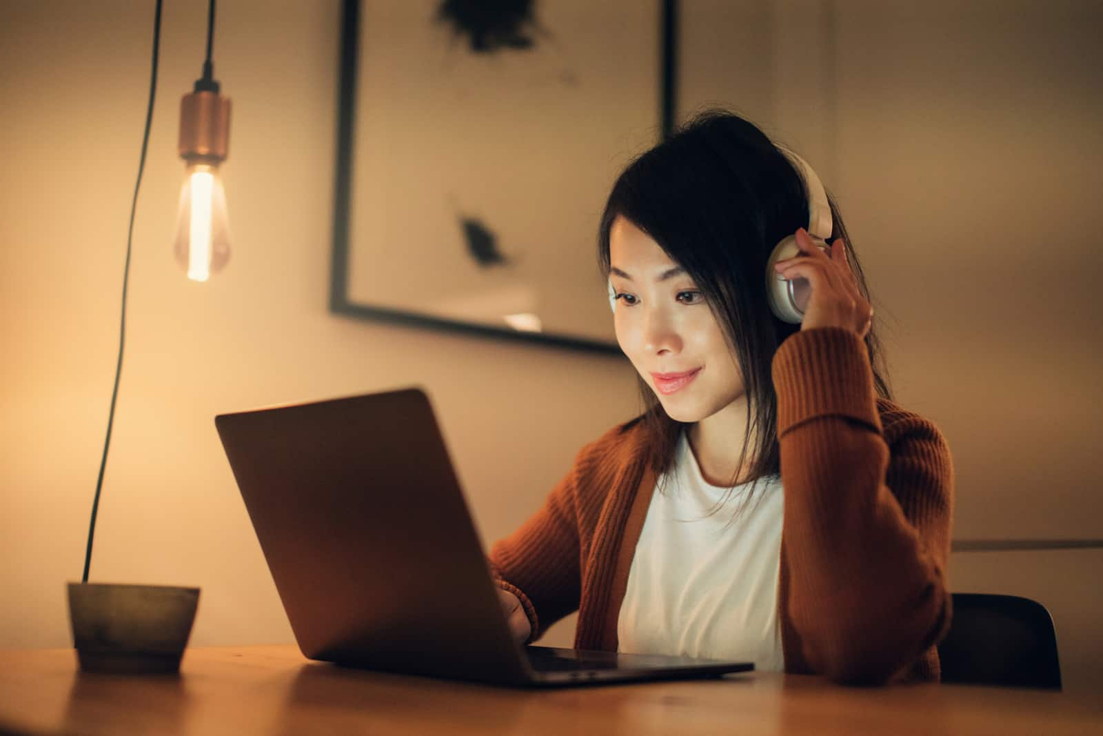 Medium shot of a young woman wearing headphones, studying online with laptop at home in the evening.