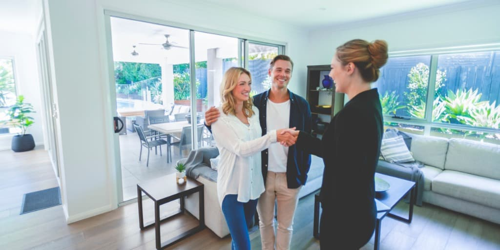 real estate agent shaking hands with couple in house