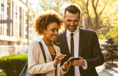 Professional woman and man using smart phone technology for real estate brokers on the go