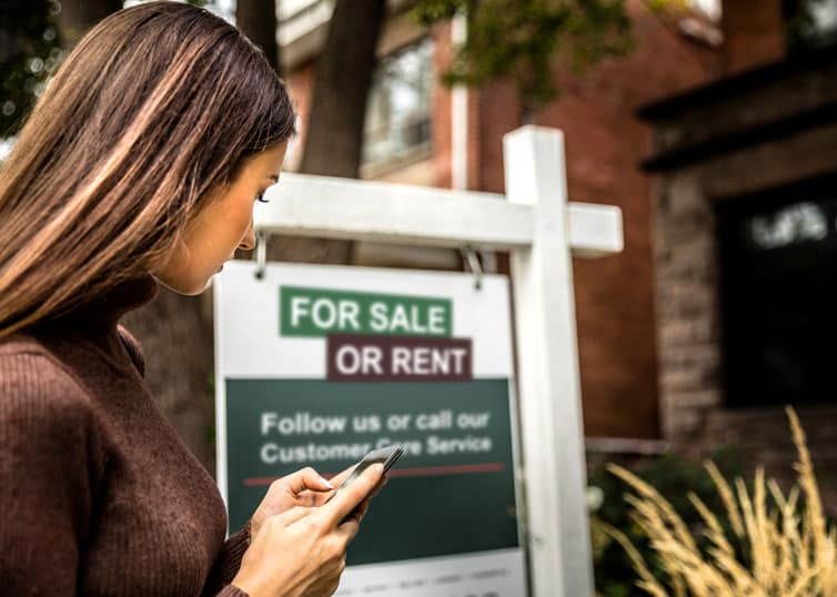 "North Carolina real estate investor checking out a property with a ""for sale or rent"" sign"