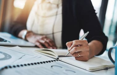 Broker writing a to-do list to help her prioritize her goals toward becoming one of the top North Carolina real estate brokers