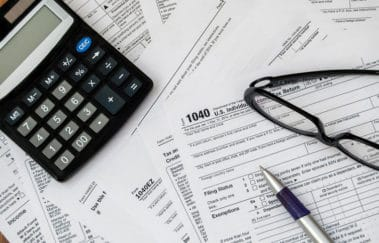 Tax forms spread out on table with calculator, pen, and eyeglasses