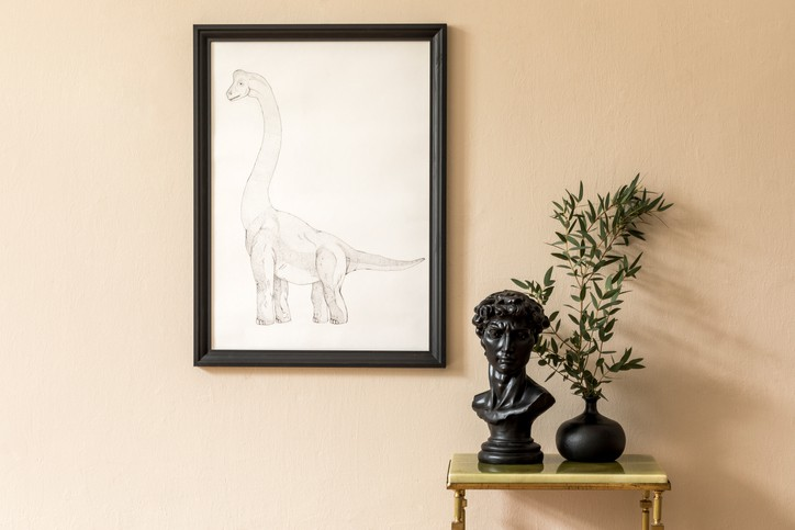 Minimalistic composition of living room interior with black mock up poster frame, green marble coffee table, flower in vase and sculpture. Beige wall. Stylish home decor. Template.