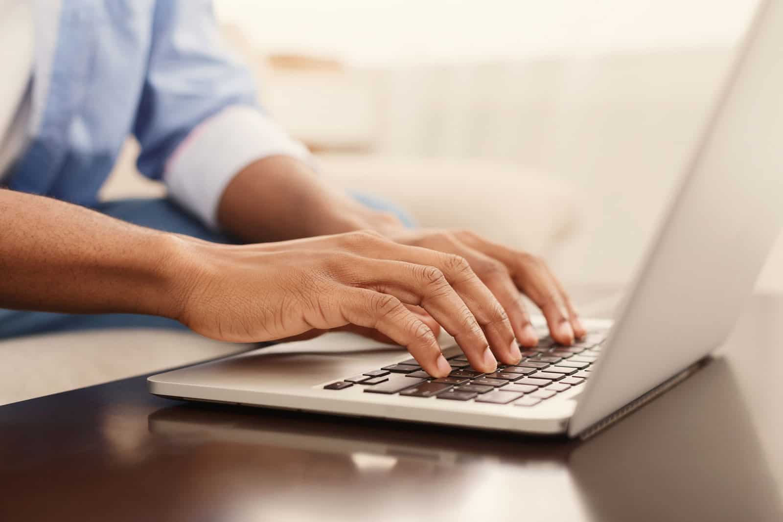 Business professional typing on laptop