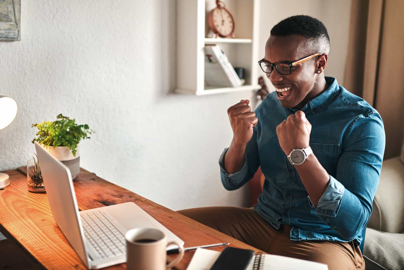 Cropped shot of a handsome young businessman sitting alone in his home office and feeling excited while using his laptop