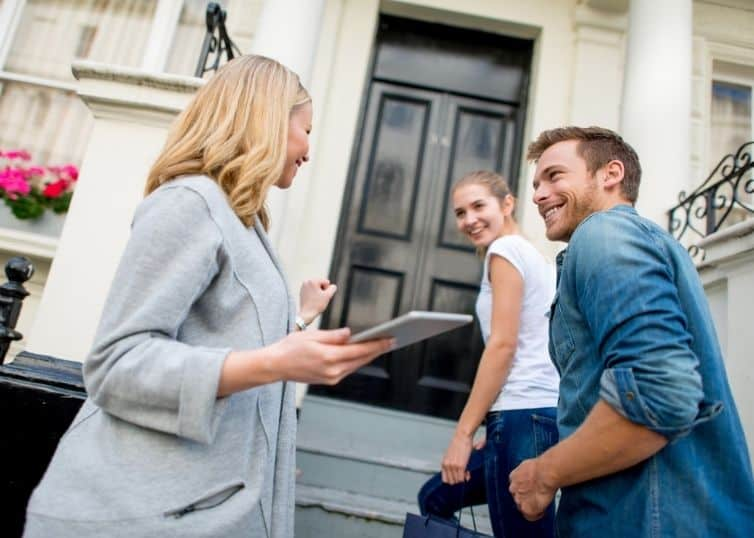 Real estate broker showing a home to a young couple