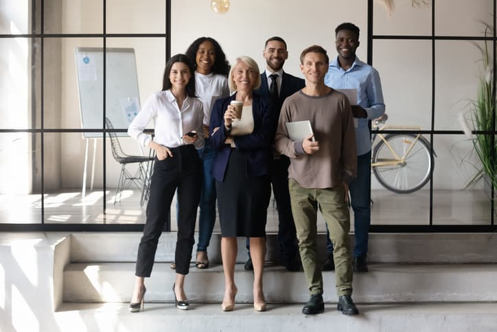 Multicultural businesspeople standing together in modern workspace