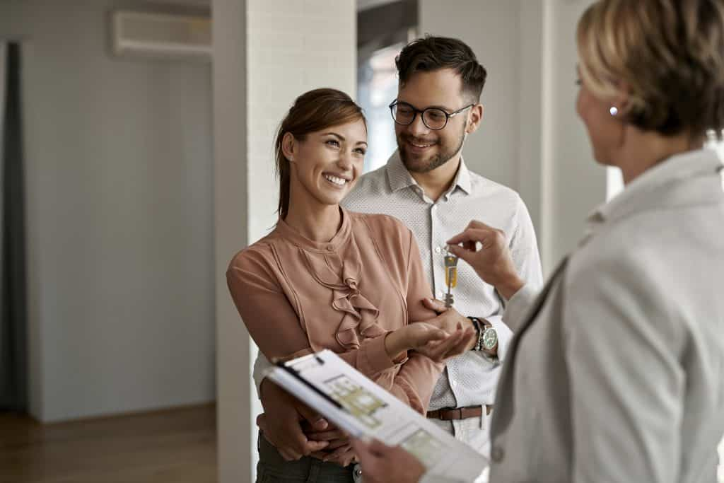 Young happy couple receiving keys of their new home from real estate agent.