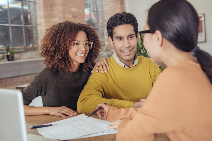 Young couple meeting with real estate professional to close a real estate transaction