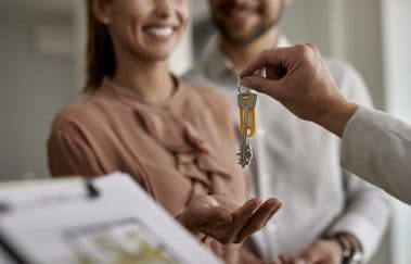 Close-up of real estate agent giving new house keys to first-time homebuyers