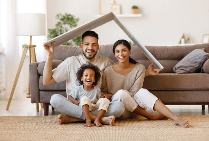 North Carolina homebuyers, parents with child smiling and roof mockup over heads while sitting on floor in cozy living room, relocation concept