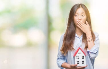 Young real estate broker holding house, covering mouth with hand, North Carolina real estate licensing pitfalls concept